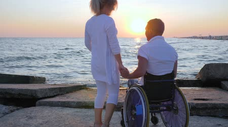 inwalida : Handicapped with pregnant girl watching sunset, spouse in wheelchair holds arm woman with big belly,