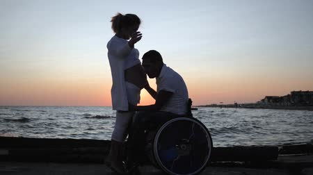 inwalida : disabled listens abdomen of his wife in evening, invalid spouse in wheelchair with pregnant female at sunset couple waiting for baby