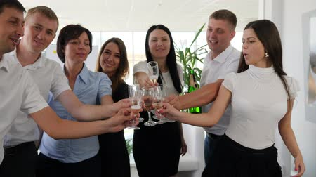 spolupracovníci : Toast in glasses with champagne into arms of Business partners on work in modern office space Dostupné videozáznamy