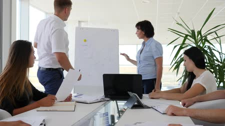 spolupracovníci : office worker shows of diagram on Whiteboard at work in bright room of business center Dostupné videozáznamy