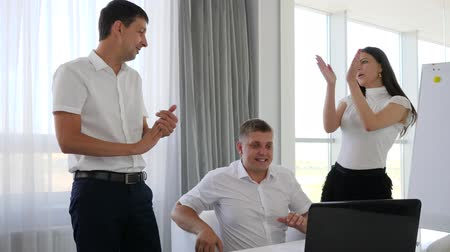 spolupracovníci : Happy Business partners clap their hands Sitting before laptop on table at work in office space