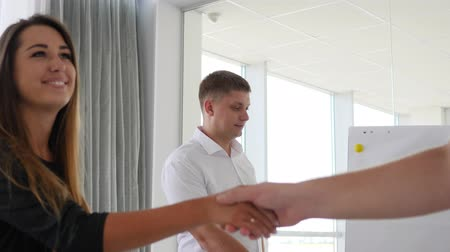 spolupracovníci : handshake close-up between collaborators on Business meeting in modern office on background large windows
