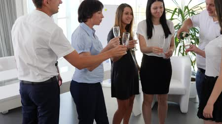 spolupracovníci : champagne bottle Into hands of businessman next to colleagues who raising toast in office space in Slow motion