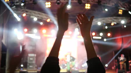 worship : hands of fans applaud on night event into bright lighting on unfocused background