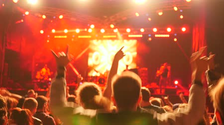 hayranlık : fans jumping with arms raised enjoy live music during rock concert illuminated by floodlights in night