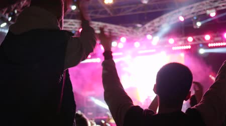 hayranlık : fans friends with arms raised clapping with pleasure at Evening event on background of stage illuminated by floodlights in Slow motion