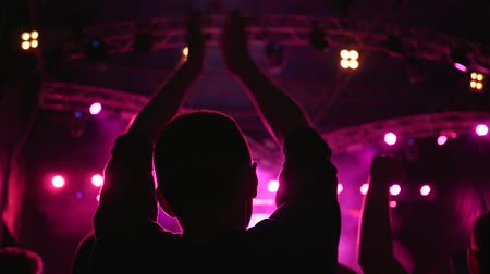 fire arms : silhouette of fans claping with arms raised over head at night festival of live music in bright illuminated by floodlights in Slow motion