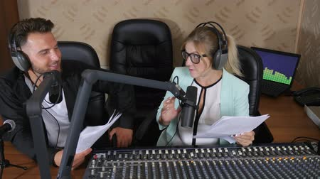 falar : nice radio presenters male and girl in headphones talks into microphone near audio console at radio show indoors Vídeos