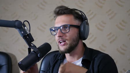 talk show : nice man radio host into glasses and headphones says into mike at studio close-up