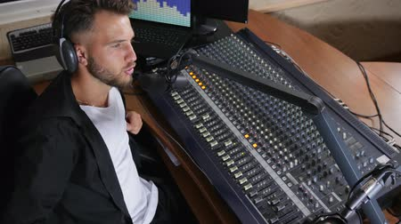 mixer : DJ with headphones on his head sit on chair and works near mixer in studio Stock Footage