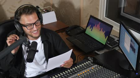 talk show : beautiful radio presenter into eyeglasses and headset at job reads news live into microphone near equipment at radio studio Stock Footage