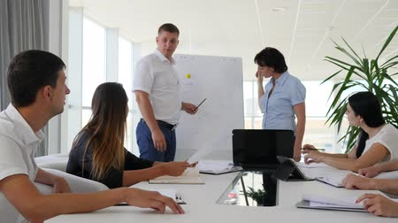 клейкий : man points on flipchart offers ideas near business people sitting at table in conference room Стоковые видеозаписи