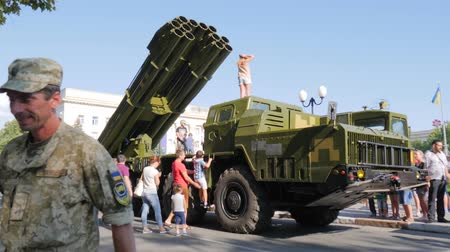 harcias : Kherson, Ukraine 24 August 2017: soldiers into uniforms walk in city among people near large military machine in Kherson, 24 August 2017 on street Stock mozgókép