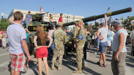 harcias : Kherson, Ukraine 24 August 2017: soldiers into military uniform among urban people near tank with large cannon in Kherson, 24 August 2017 into center of city in summer