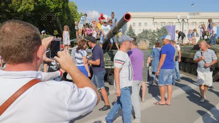 harcias : Kherson, Ukraine 24 August 2017: man with phone into hands takes picture of crowd of children on military tank in Kherson, 24 August 2017 on street at city center in summer