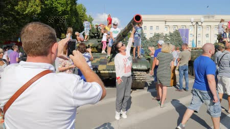 harcias : Kherson, Ukraine 24 August 2017: male with mobile into hands takes photo of inhabitants of city and children on military tank in Kherson, 24 August 2017 to street in summer