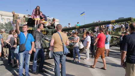 harcias : Kherson, Ukraine 24 August 2017: lot of children and adults are viewing and taking pictures on gadgets near large tank in Kherson, 24 August 2017 against blue sky Stock mozgókép