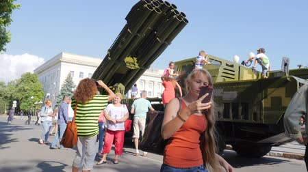 harcias : Kherson, Ukraine 24 August 2017: long-haired girl with smartphone into hands makes selfie on background of military machine in Kherson, 24 August 2017 in city center on street Stock mozgókép
