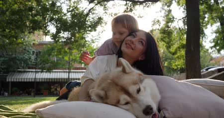 hound : family and pet, young mother with child lie near husky dog on background of nature close-up in park