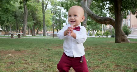gentleman : adorable baby making first steps barefoot on green grass at park outdoors, happy childhood
