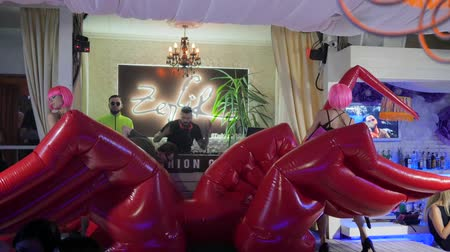 peruca : Kherson, Ukraine 12 August 2017: Miss Zefir Event girls in pink wigs and high heels are dance on stage in nightclub, dj into Sunglasses at evening party in Kherson, 12 August 2017. night life of modern youth,
