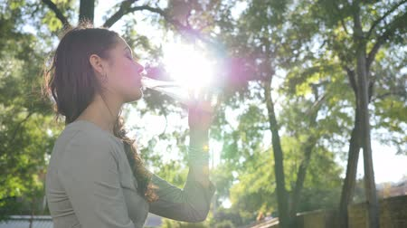 fortunate : girl with braces drinks clean water from a glass bottle in backlight and smiles on background trees in park