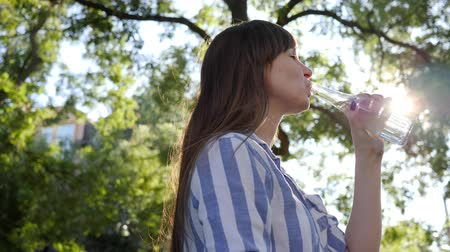 fortunate : female drinks cold mineral water from a glass bottle in backlight and smiles at sunny day on nature Stock Footage
