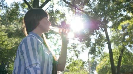 fortunate : pretty female drinks cold mineral water from glass bottle and smiles outdoors in backlight on background green trees at park Stock Footage