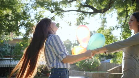 fortunate : lucky girls holding hands whirling with colorful balloons having fun on background green trees, emotions in backlight