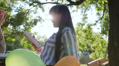 fortunate : joyful female with colorful balloons congratulates friend happy birthday in park, presents surprise in sunny day Stock Footage