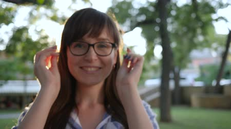 giyme : happy female put on stylish glasses and smiling on camera at park, close-up in backlight