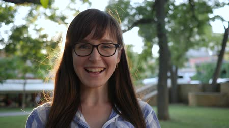 espetáculos : girl puts on eyeglasses at park outdoors and smiling on camera in backlight Stock Footage