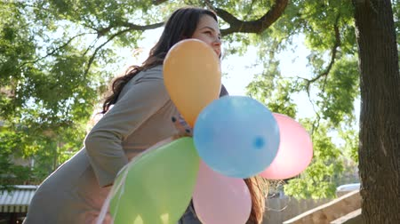 fortunate : emotions in sunny day, joyful female with colorful balloons congratulates friend happy birthday in park and presents surprise