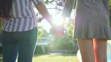 bilezik : rear view of two unrecognizable girls holding hands with LGBT bracelet in backlight stand in park on background green trees