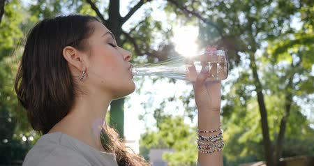 zuby : thirsty female with braces on teeth drinks clean water from a glass bottle on the background green trees at sunny day Dostupné videozáznamy