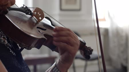 podfuk : hands of a woman holding fiddle with fiddlestick and playing on concert close-up indoors