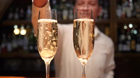 desfocado : male barman throws an wedding ring in goblet with champagne close-up in cafe