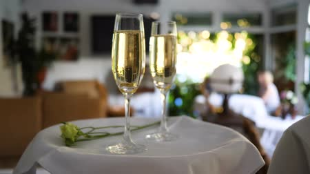 złoto : glasses with ring at bottom in champagne on white tray with floret in cafe on unfocused background at romantic event Wideo
