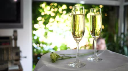 pohárek : goblet with gold ring in champagne on white tray with blossom in restaurant on unfocused background close-up