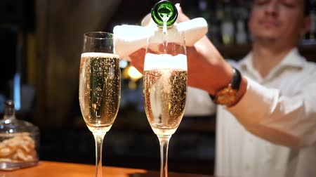 pohárek : bartender pours sparkling champagne in glasses with white foam close-up