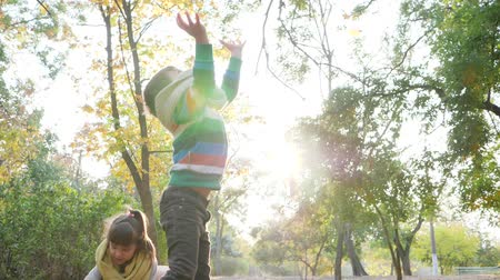 dvojčata : cheerful kids playing in backlight on nature, throw yellow leaves into the air in autumn park
