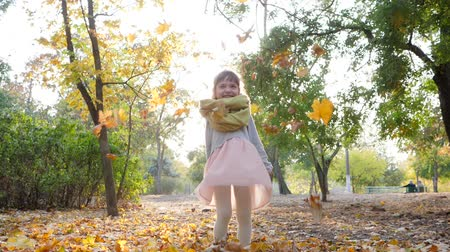 caráter : autumn, small girl in backlight outdoors throws yellow leaves in slow motion at city park Stock Footage