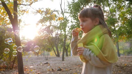 sabão : pretty kid making bubbles outdoors on background of sun and trees in autumn park