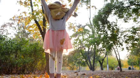 throws : beautiful little girl jumps and throws yellow leaves in backlight at autumn park in slow motion Stock Footage