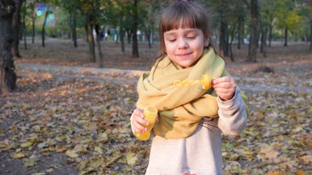 caráter : pretty kid making iridescent soap bubbles into camera outdoors autumn, slow motion Stock Footage