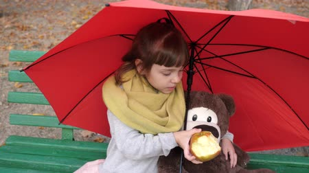 útil : little girl and toy friend sit on a bench in park under an umbrella and eats large red apple