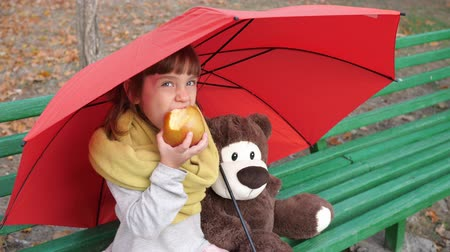 плюшевый мишка : cute little girl eats large red apple near to teddy bear on wooden bench under an umbrella on nature autumn