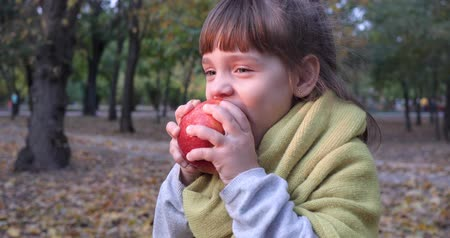 come : nice female child smiles and bites an apple on background of yellow foliage in autumn outside