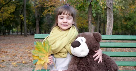 peluş : little girl sitting on bench with teddy bear and leaves in hands posing at camera on background autumn park