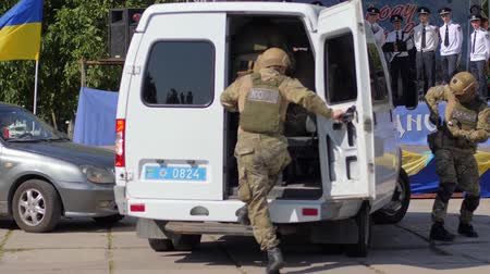 climbed : Kherson, Ukraine, 5 August 2017: military training group of armed soldiers in masks climbed into large white car in Kherson, 5 August 2017 on street Stock Footage